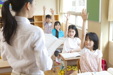 Elementary school students to a show of hands in class