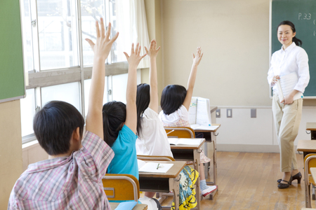 From behind four elementary school students to the show of hands in class Stock Photo