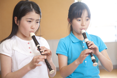 Elementary school girls blow the recorder