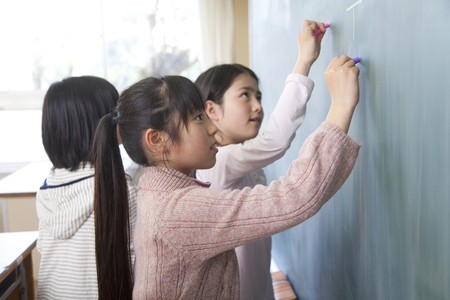mischief: Elementary school girls draw pictures on the Blackboard