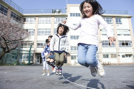 onderwijs: Basisschool leerlingen en leerkrachten om een grote springtouw