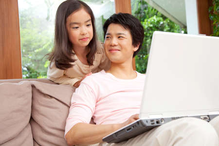 nuclear family: Father and daughter to see the monitor of a laptop