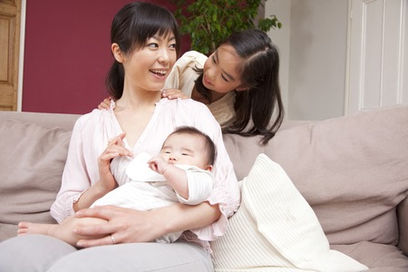 Daughter to put a hand on her mothers shoulder to hug the baby