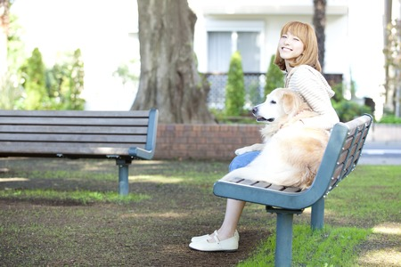 take a break: To take a break and sit on the bench smiling woman with Golden Retriever Stock Photo
