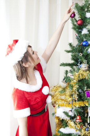 decorate: Santa girl to decorate a Christmas tree