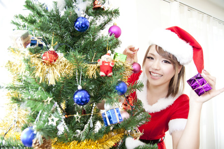 santa girl: Santa girl to decorate a Christmas tree