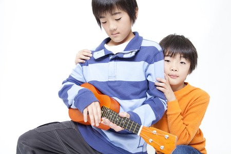 boy kid: Brother to play a musical instrument