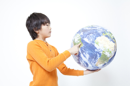young fellow: Boy pointing at the globe Stock Photo