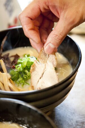 serving dish: Hand to place  in a serving dish ramen