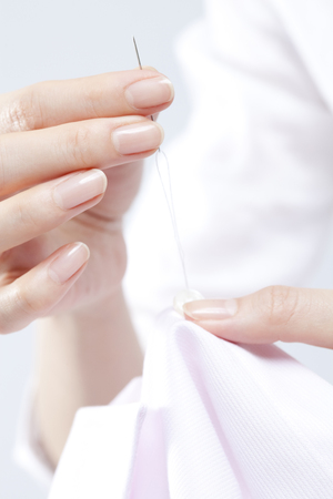 suture: Hands of women sewing Stock Photo
