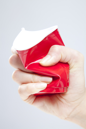 crush on: Mano aplastar el vaso de papel Foto de archivo