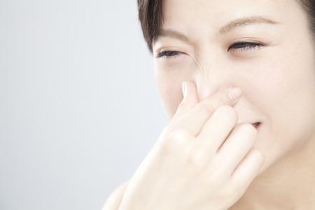 stinking: Women hold ones nose Stock Photo