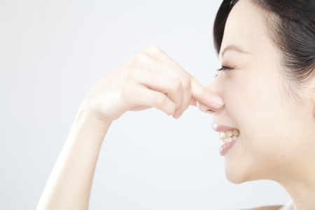 the stinking: Women hold ones nose Stock Photo