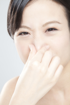 stench: Women hold ones nose Stock Photo