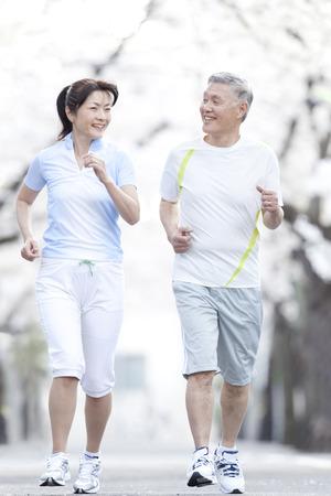 asian trees: Senior couple jogging