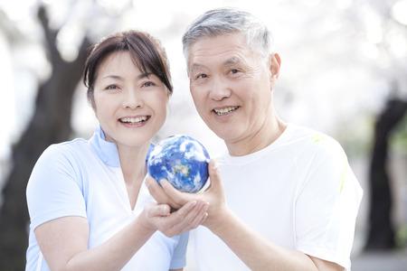 holding globe: Senior couple holding globe
