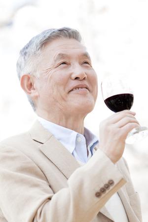 年配の男性がワインを浮かべて 写真素材