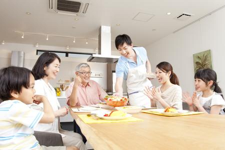 ni�os cocinando: Alrededor de la familia de tres generaciones de mesa
