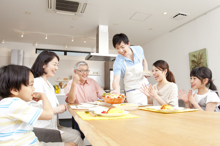 asian old man: Surrounding the table three generation family Stock Photo