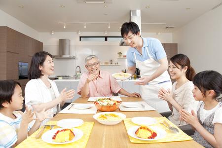 Surrounding the table three generation family Foto de archivo
