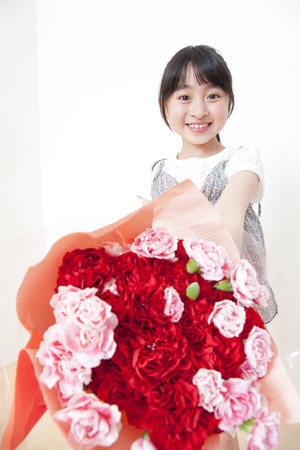 Girl hold out a carnation Stock Photo