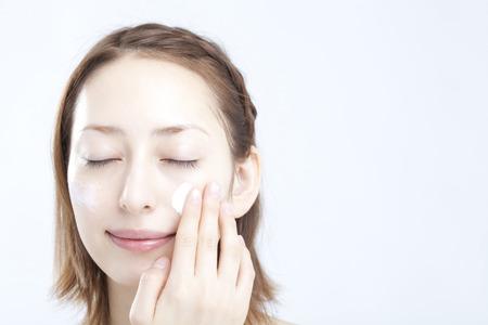 Women applying base cream Stock Photo