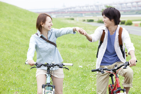 Men and women who ride a bike hand in hand Stock Photo