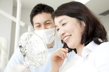 Female patient look in the mirror in the dental clinic Stock Photo