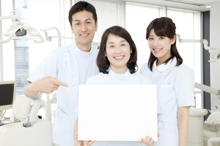 Dentist and dental hygienist with a message board