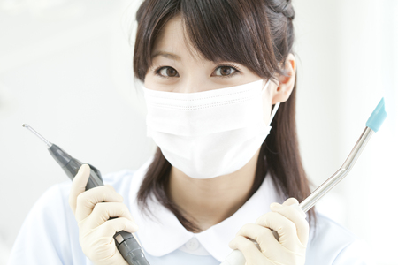 Dental hygienist with the treatment instrument