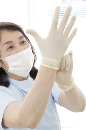 Dentist to fit the rubber gloves Stock Photo