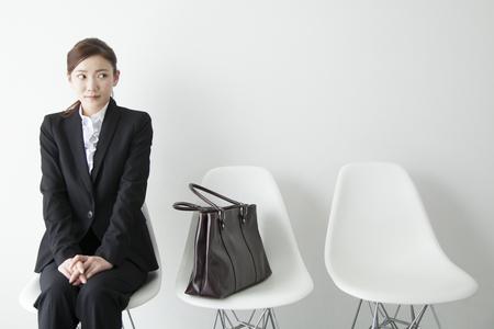 椅子に座って緊張する OL