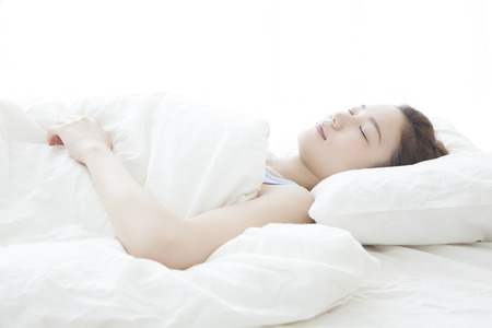 Woman sleeping in a bed Stock Photo