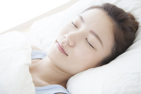Woman sleeping in a bed Stock fotó