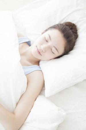 niño durmiendo: Mujer que duerme en una cama Foto de archivo