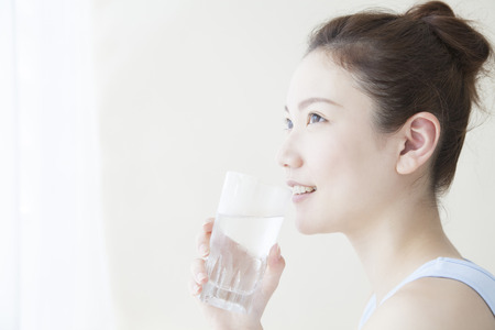 young man smiling: Woman drinking water Stock Photo