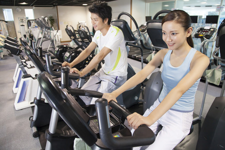 Men and women to train in the exercise bike Imagens