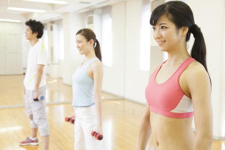 gimnasia aerobica: Los hombres y las mujeres en el ejercicio de mancuernas Foto de archivo
