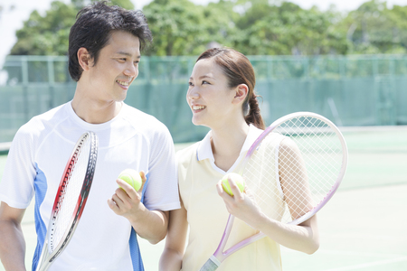 Men and women smiling at the tennis court