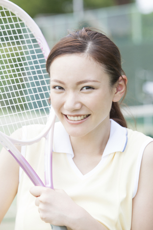 tennis racket: Woman holding tennis racket