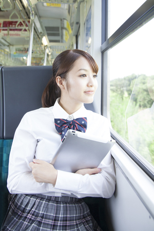 High school girls with a tablet PC in the seat of a train