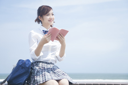 High school girls to be reading at the seaside Stock Photo
