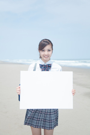High school girls with a message board on the beach Stock Photo