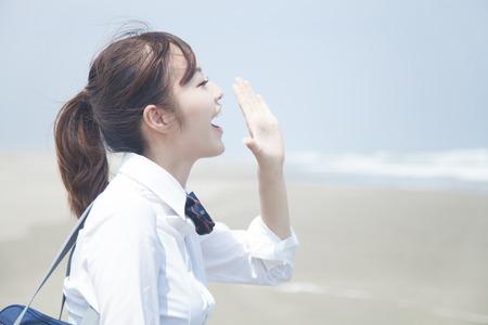 海に向かって叫んでいる女子高校生
