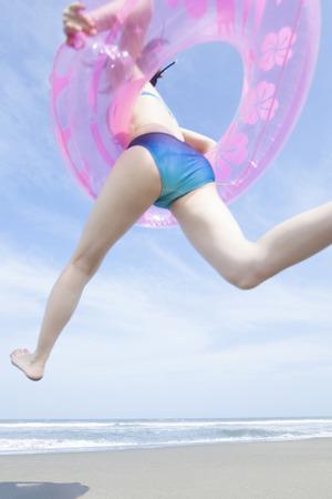 inner tube: Woman running into the sea wearing the inner tube