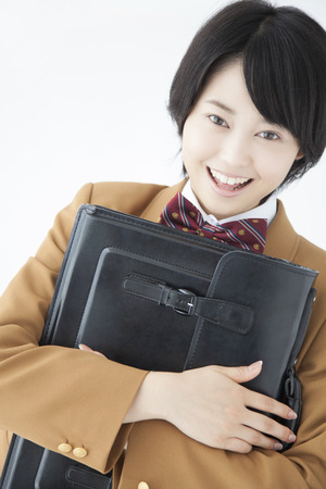 satchel: High school girls to smile with a satchel Stock Photo
