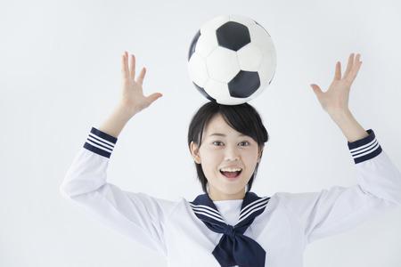 junior soccer: Junior high school girls to put a soccer ball on his head Stock Photo
