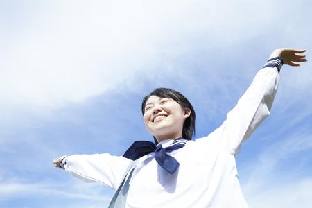 Middle school girls to widen the hands under the blue sky Foto de archivo