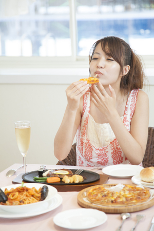 kafe: Woman eating pizza at the restaurant