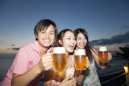 Men and women drink beer at the beach